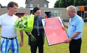 Van Mariahout (links) overhandigt de koper van het honderdste shirt een ingelijst exemplaar.